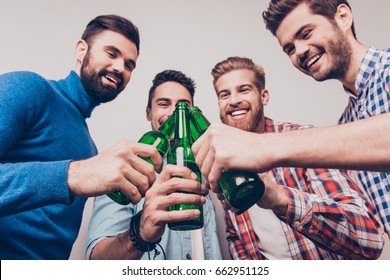 Cheers men! Bachelor men`s life. Low angle photo of four happy friends, clinking their glasses of beer. They are fans of sports games as football, basketball, hockey, baseball