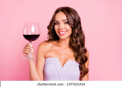 Cheers! Portrait of nice sweet tender gentle adorable attractive gorgeous flirty cheerful wavy-haired brunette girl with decollete, holding wine-glass, isolated over pink background