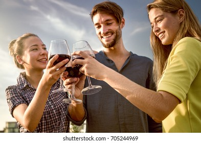 cheers with red wine drinking friends celebrating at outdoor party. happy and smiling 2 girls and 1 man tasting sangria wine under open sky