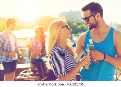 Cheers! Smiling young couple clinking glasses with beer and looking at each other while two people barbecuing in the background
