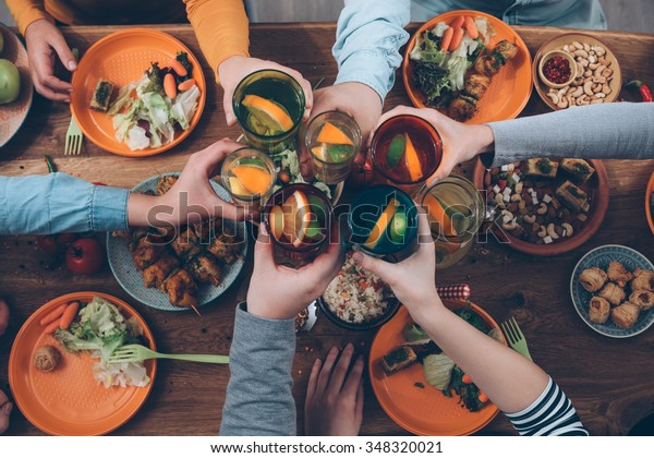Cheers! Top view of people cheering with drinks while sitting at the rustic dining table