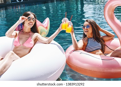 Cheers! Two beautiful and happy young women in swimwear drinking orange fresh while relaxing in the pool