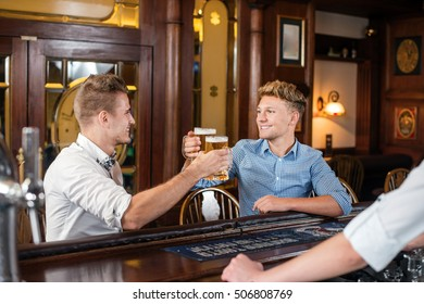 Cheers. Two friends sitting in the pub. Friends clinking glasess with beer and looking on each other