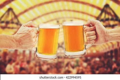 cheers, two glass beer mugs in hands