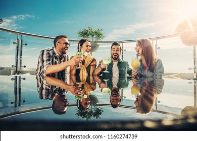 Cheers. Two young couples spending time at rooftop bar with alcohol drinks. They are toasting and laughing