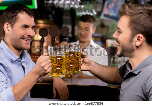 Cheers! Two young men drinking beer in bar