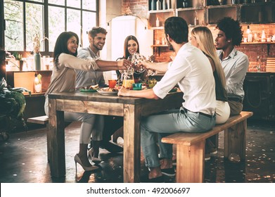 Cheers to us! Group of cheerful young people cheering with champagne flutes and looking happy while while sitting at the dinning table together