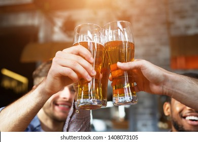 Cheers For Us. Men Drinking Draft Beer And Clinking Glasses At Pub, Closeup