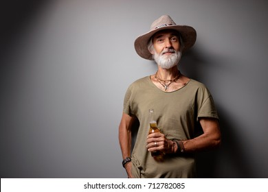Cheers! Vacation concept. Studio portrait of handsome senior man with gray beard and hat holding bottle of beer.
