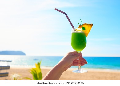 Cheers vacation! Taking exotic cocktail in hand. Summer landscape on sunny day is on the background.