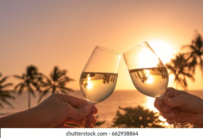 Cheers with wine glasses in a beautiful sunset beach setting.