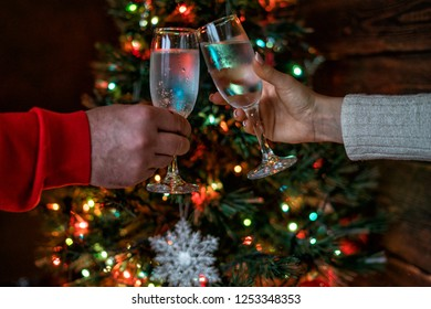 Cheers! Womam and man cheering with champagne flutes on the Christmas interior in the background. Holidays concept. Evening lights glowing. New Year celebration. Toned image. Selective focus.