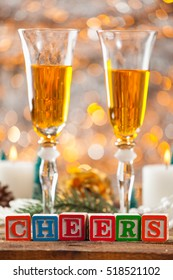 Cheers Written With Toy Blocks On Christmas Card Vertical Background With Champagne And Copy Space.