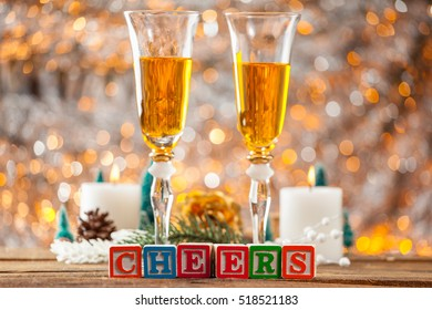 Cheers Written With Toy Blocks On Christmas Card Background With Champagne And Copy Space.
