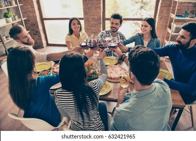 Cheers! Young happy multiethnic friends are toasting at the birthday party at home. All wearing casual clothes and having fun together