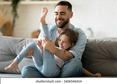 Cheery father spend time with little daughter family enjoy playtime on weekend together seated on couch at home laughing feels overjoyed, dad and kids girl having fun indoors, happy fatherhood concept
