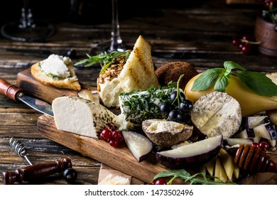 Cheese appetizer selection. Red currant, honey, basil, grapes and nuts on rustic wooden board over wooden concrete backdrop, top view. Belper Knolle, goat cheese, Scamorza. Cheese board, cheese plate.