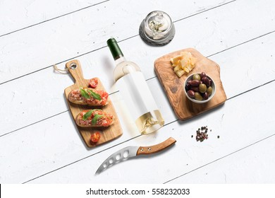 Cheese appetizer selection or wine snack set. White wine, variety of cheese, bread, olives on wooden board over white backdrop, isometric view, copy space