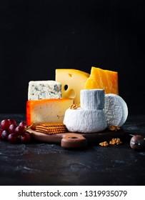 Käsesortiment: blauer Käse, Hartkäse, Weichkäse auf einem Schnittbrett. Schieferschwarzer Hintergrund. Kopiert Platz.