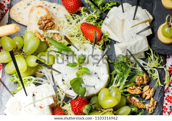 Cheese assortment plate on dark wooden background, free space. Top view on plate with snack on for wine