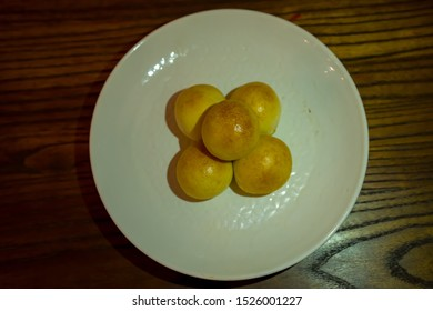 Cheese Balls in the blurry background, the small bite pastry in ball shape stuffed with mozzarella cheese. Stacking on the round white plate, on the wooden table.