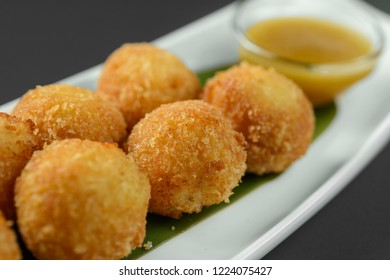 Cheese balls on narrow plate arranged with sauce on dark background