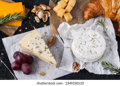 Cheese banner - blue cheese, camembert, cheddar and parmesan tasting with grapes and rosemary. Food banner for text or design. Top flat view photo, overhead.