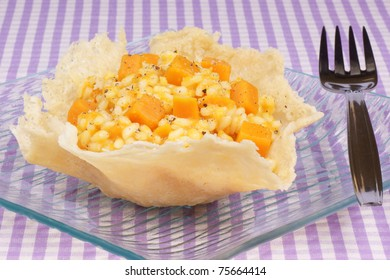 Cheese basket filled with risotto and pumpkin over a glass dish