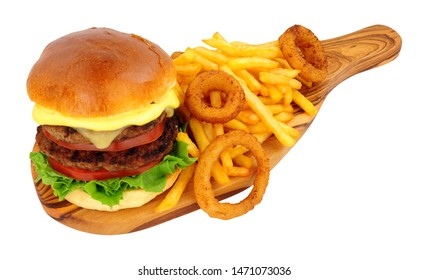 Cheese beef burger and French fries with battered onion rings on an olive wood serving board isolated on a white background