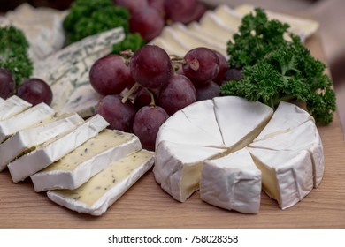 Cheese board: Camembert with herbs decorated with grapes and parsley