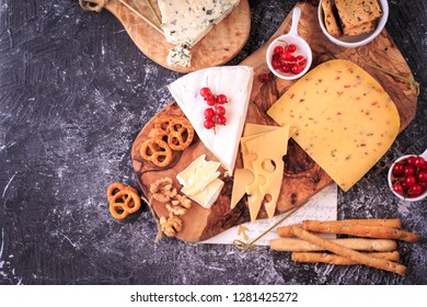 Cheese Board. Cheese and cracker appetizer selection over dark backdrop, top view.