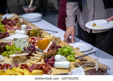 cheese board with different cheeses fruits breads and cold meat selection out of focus grain