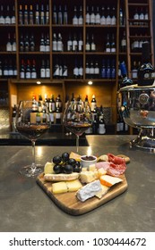 Cheese board in first plan with a wall of French wine on the back.