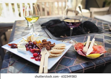 Cheese board with fruit and nuts and meat plate with salmon and salami and glass of red and white wine at winery tasting