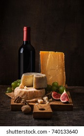 Cheese board, fruits and wine on the rough wood