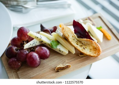 Cheese board with grapes and dried fruits (selective focus)
