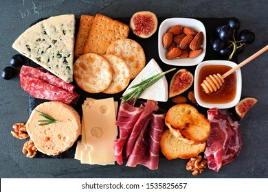 Cheese board with a selection of cheeses and meats. Top view on a dark slate background.