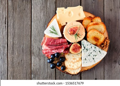 Cheese board with a selection of cheeses and meats. Top view on a rustic wooden background.