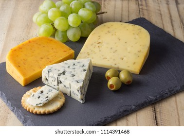 Cheese board with three cheeses, gouda with pimento, gouda with cumin seeds and roquefort blue cheese close up on rustic wooden background