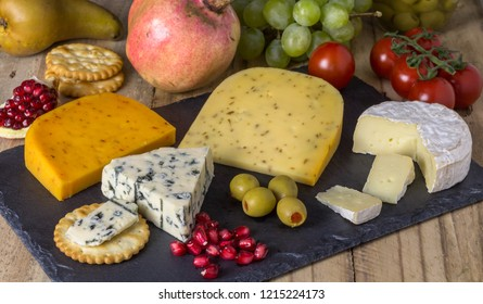Cheese board with three cheeses, gouda with pimento, gouda with cumin seeds and roquefort blue cheese  and camembert close up on rustic wooden background