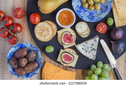 Cheese board with three cheeses, gouda with pimento, gouda with cumin seeds and roquefort blue cheese  and assorted fruits close up on rustic wooden background