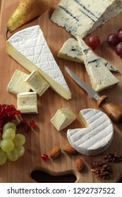 Cheese board with various types of cheeses served with fruits and nuts