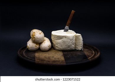 Cheese bread and brazilian minas white cheese on a wooden cutting board isolated in dark background