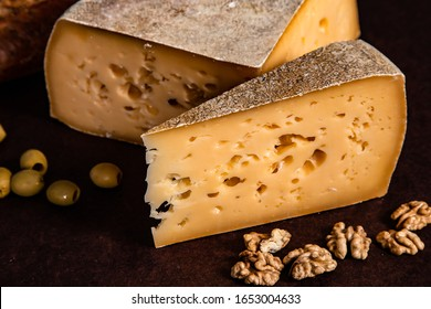 Cheese, bread and nuts on a dark background