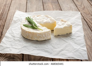 Cheese. Brie. Camembert. French, Italian cheese. Slice of cheese on a wooden table. Cheese on a wooden background.
