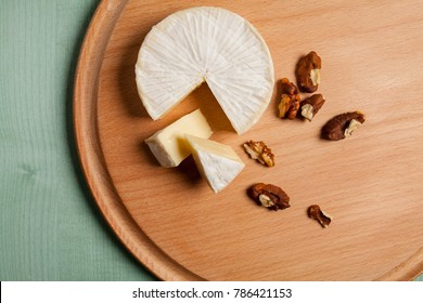 cheese brie camembert and walnuts, on a wooden light background. view from above. Camembert cheese. Cheese brie camembert on a light wooden background. Food for wine and romance. Text space.