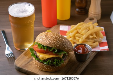 cheese burger with beer and french fries on wooden board