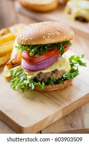 cheese burger and french fries for meal on wooden board