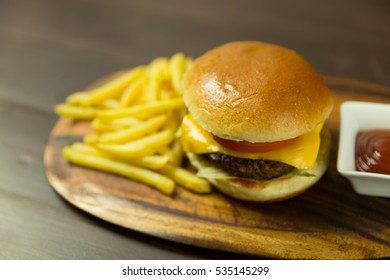 Cheese burger with fries and red sauce on wood serving board