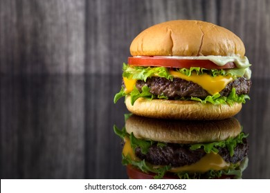 Cheese burger with lettuce , tomato and mayonnaise on glossy black table and wooden background